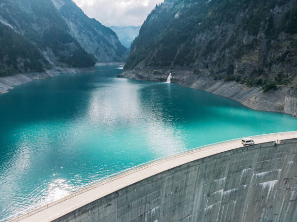aerial view of white camper van crossing dam in swiss alps - diga foto e immagini stock