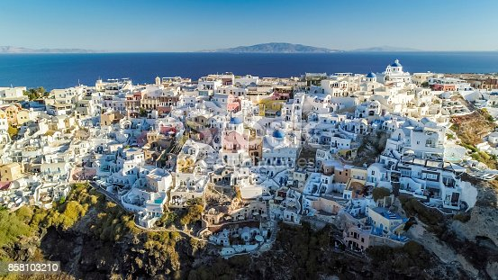 istock Aerial view of white houses and blue dome churches in Oia, Greece 858103210