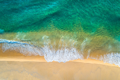 Aerial view of white sand beach coastline and swirling waves with teal blue ocean