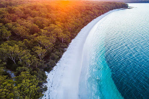 Aerial view of white sand beach coastline with teal blue ocean and golden light