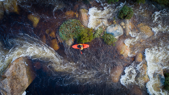 Aerial image of a white water kayaker on a mountain river in flood after good winter rains in south africa
