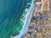 Aerial drone photography showing Windansea Beach and a neighborhood of homes in La Jolla, California. La Jolla is a town in San Diego, situated along the Pacific Ocean.