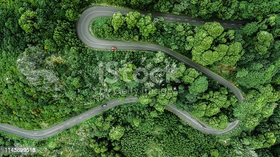 istock Aerial view of winding road trough the dense woods on the high mountain. 1143699518