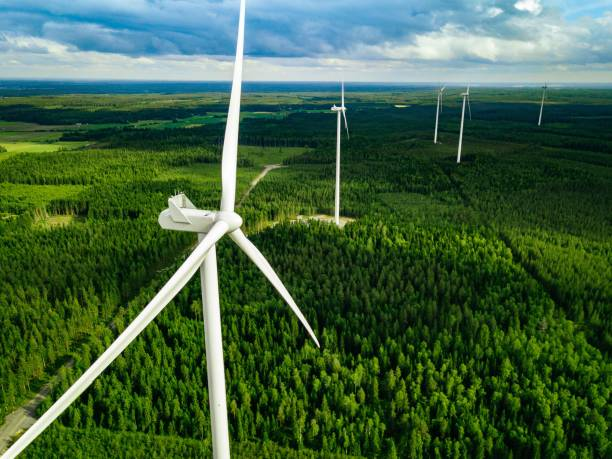 Aerial view of windmills in summer forest in Finland. Wind turbines for electric power with clean and Renewable Energy Aerial view of windmills in green summer forest in Finland. Wind turbines for electric power with clean and Renewable Energy windmill stock pictures, royalty-free photos & images
