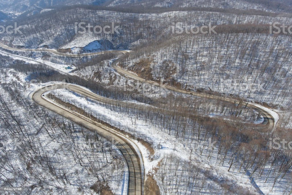 Aerial view of winter mountain road in the woods stock photo