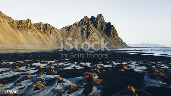 Drone photo of couple in red jackets meeting bright sunrise above Vestrahorn mountain and Stokksnes beach with huge sand dunes during wintertime in Iceland