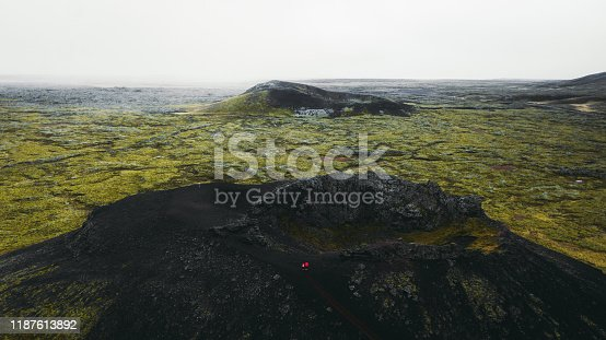 Drone photo of couple in red jackets staying in the crater of a big greeen-black volcano looking at lava fields on Snaefellsnes Peninsula in West Iceland