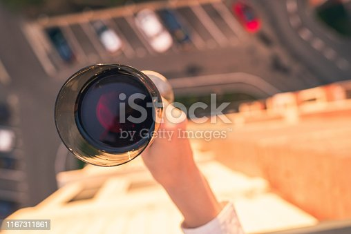 Aerial view of woman hand with glass of red wine on the city car parking and street background. Sunset