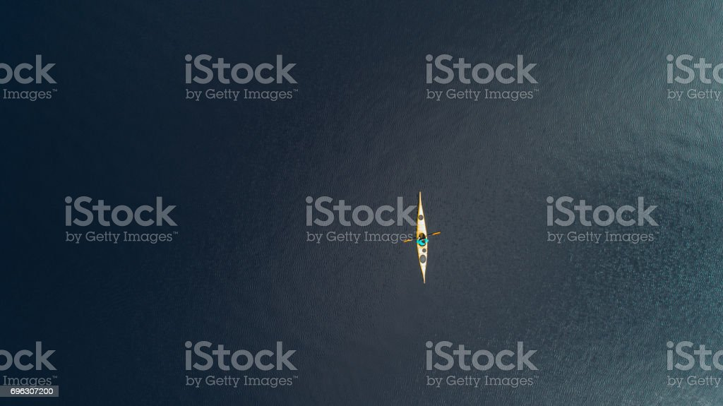 Aerial view of woman kayaking on the lake in mountains stock photo