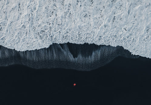 Aerial view of woman  in red coat standing on black sand beach in Iceland and looking at the sea