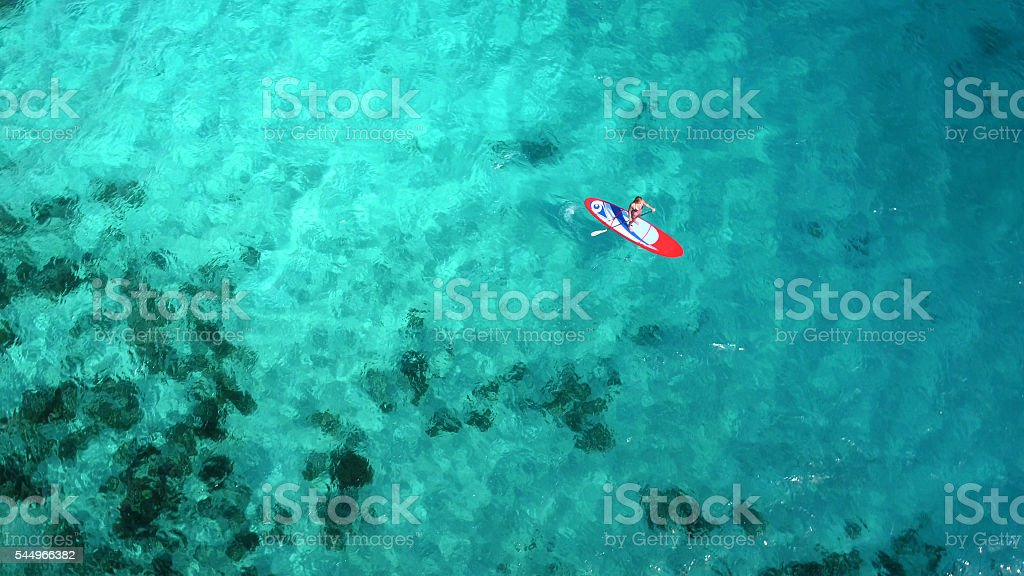 Aerial view of woman on paddleboard​​​ foto
