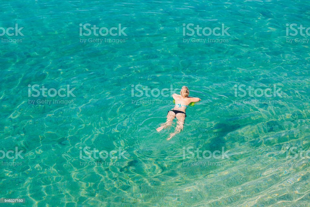 Aerial view of young blonde woman swimming in the transparent turquoise sea. Top view of slim lady relaxing on her holidays. stock photo