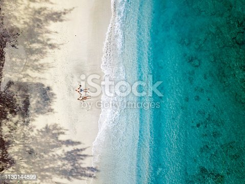 Aerial View of Young Couple Relaxing on Beach in Indonesia.