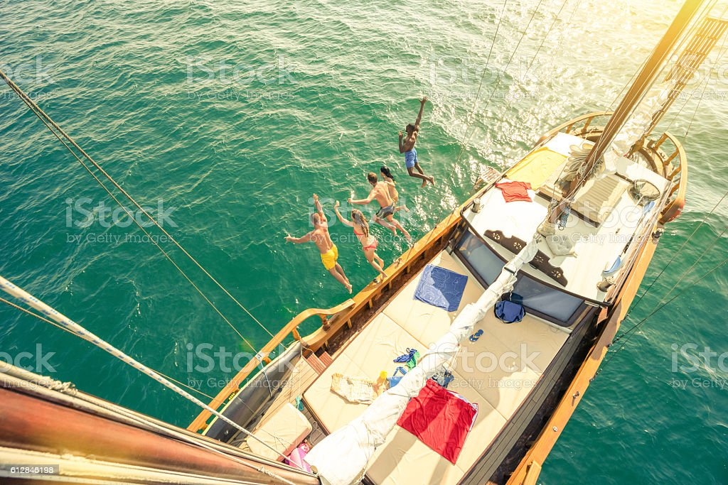 Aerial view of young people jumping from sailboat sea trip stock photo