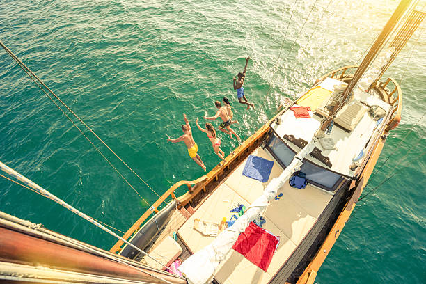 aerial view of young people jumping from sailboat sea trip - kreuzfahrt themenpartys stock-fotos und bilder
