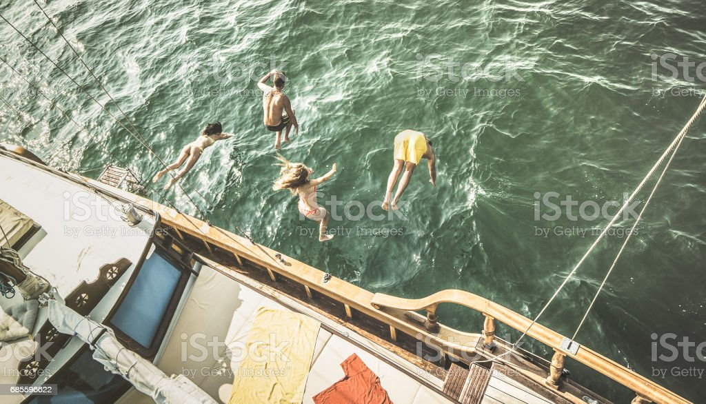 Aerial view of young people jumping from sailing boat on sea trip - Rich happy friends having fun in summer sailboat party day - Exclusive luxury vacation concept - Retro contrast desaturated filter stock photo