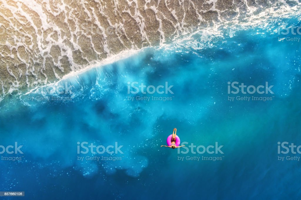 Aerial view of young woman swimming on the pink swim ring in the transparent turquoise sea in Oludeniz,Turkey. Summer seascape with girl, beautiful waves, blue water at sunset. Top view from drone stock photo