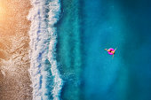 Aerial view of young woman swimming on the pink swim ring in the transparent turquoise sea in Oludeniz. Summer seascape with girl, beach, beautiful waves, blue water at sunset. Top view from drone