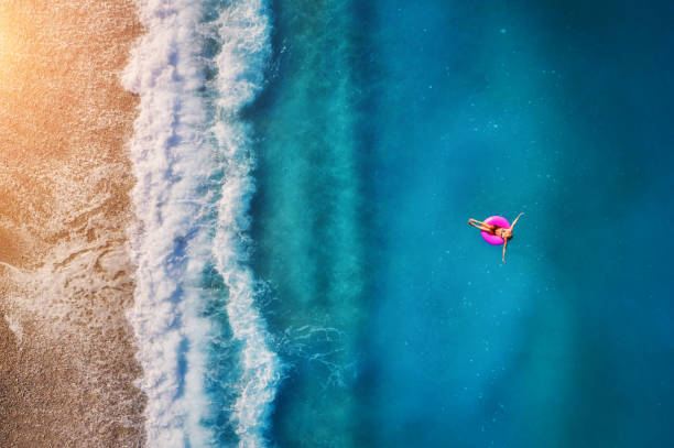 Aerial view of young woman swimming on the pink swim ring in the transparent turquoise sea in Oludeniz. Summer seascape with girl, beach, beautiful waves, blue water at sunset. Top view from drone stock photo