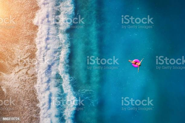 Photo of Aerial view of young woman swimming on the pink swim ring in the transparent turquoise sea in Oludeniz. Summer seascape with girl, beach, beautiful waves, blue water at sunset. Top view from drone
