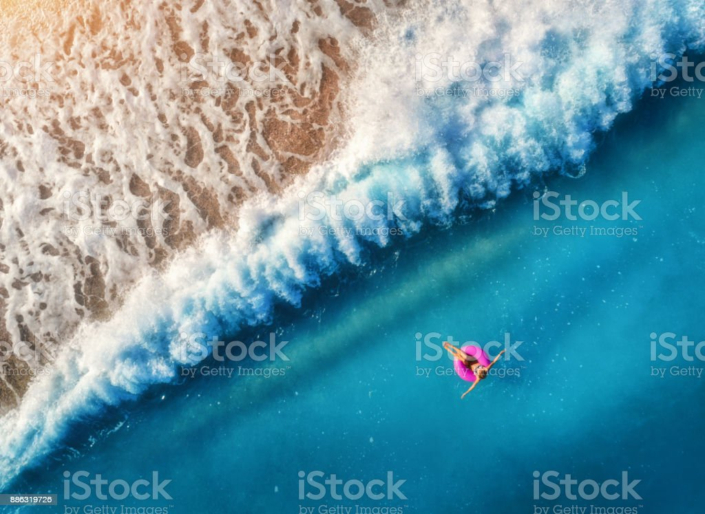 Aerial view of young woman swimming on the pink swim ring in the transparent blue sea in Oludeniz,Turkey. Summer seascape with girl, beautiful waves, azure water at sunset. Top view from drone. Travel stock photo
