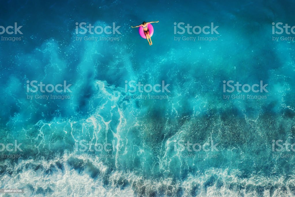 Aerial view of young woman swimming on the pink swim ring in the transparent turquoise sea in Oludeniz,Turkey. Summer seascape with girl, beautiful waves, azure water at sunset. Top view from drone stock photo