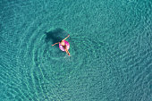 Aerial view of young woman swimming on the pink swim ring in the transparent turquoise sea at sunrise in Thailand. Summer seascape with girl, clear water in the morning. Top view. Travel and holiday
