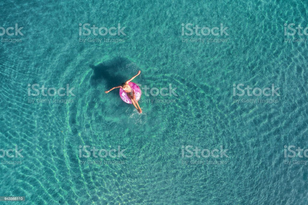 Aerial view of young woman swimming on the pink swim ring in the transparent turquoise sea at sunrise in Thailand. Summer seascape with girl, clear water in the morning. Top view. Travel and holiday stock photo