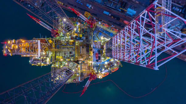Aerial view offshore jack up rig  at night, Offshore oil rig drilling platform. stock photo