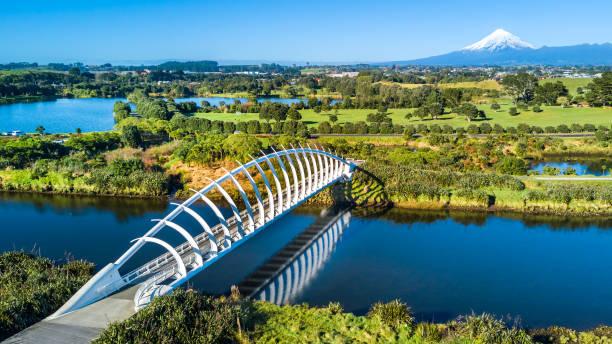 공중 보기 작은 개울 건너 아름 다운 다리에 마운트 타 라 나 키와 배경에. 뉴질랜드 - 태즈먼 해 뉴스 사진 이미지