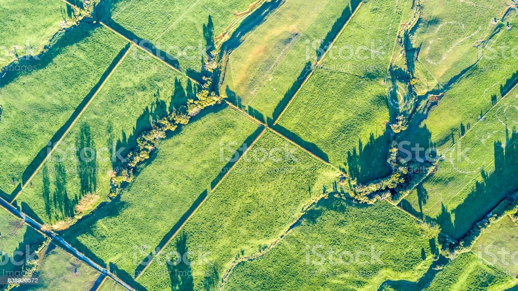Aerial view on a farmland with roads and livestock paddock on a slops hills near New Plymouth. Taranaki region, New Zealand stock photo