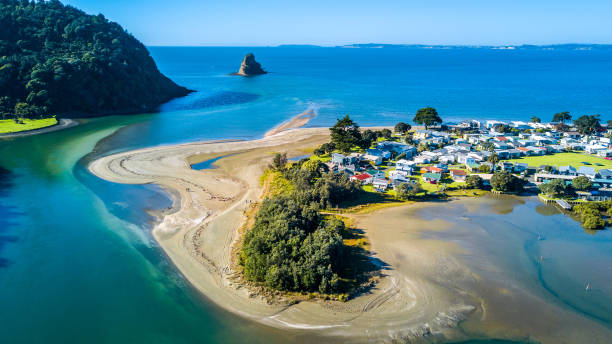 Aerial view on a river mouth with residential suburb on the shore and ocean with small islands on the background. Auckland, New Zealand stock photo