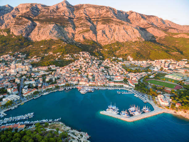 Aerial view on Makarska and marina at sunset with Biokovo mountain in background (Croatia). stock photo