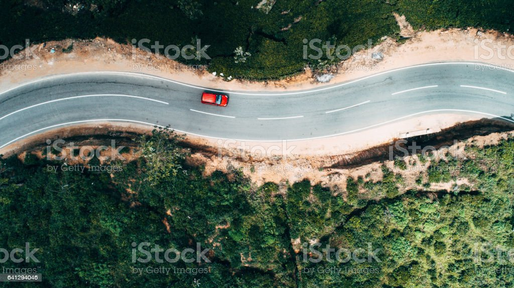 Aerial view on red car on the road near tea plantation Aerial view on  red car on the road near green tea plantation in mountains in Sri Lanka Above Stock Photo