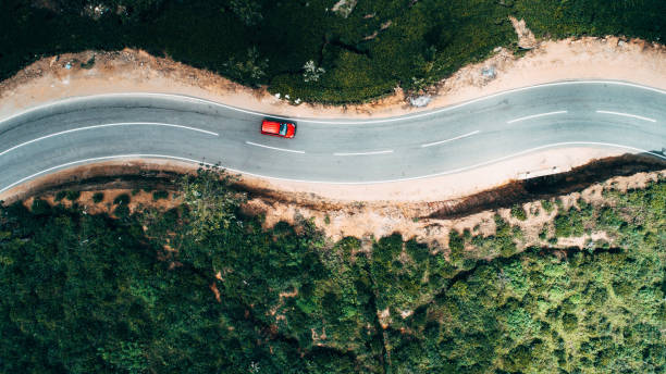 Aerial view on red car on the road near tea plantation Aerial view on  red car on the road near green tea plantation in mountains in Sri Lanka car stock pictures, royalty-free photos & images