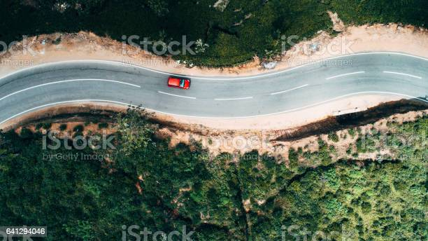Photo of Aerial view on red car on the road near tea plantation