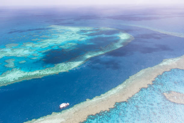 aerial view on sea channel with scuba diving tourist boat through great barrier reef near airlie beach surrounded by shallow coral reef in turquise clear water. - great barrier reef marine park stock pictures, royalty-free photos & images