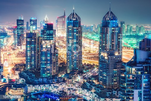 istock Aerial view on skyscrapers and highways of Dubai Marina, UAE. Multicolored travel background. 1047089368
