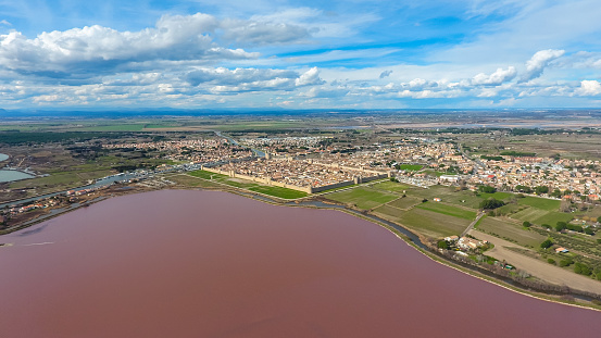 Aerial view on the pink salt lake and Aigues-Mortes - the town behind the stone fortification wall