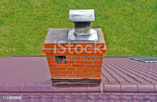 Aerial view on traditional brick chimney in red color with ventilation hole and steel pipe from furnace.
