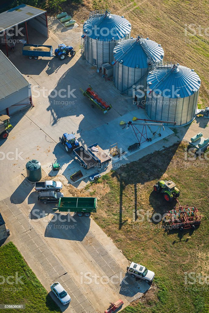 Aerial view onto modern farmyard agricultural machinery tractors and silos stock photo