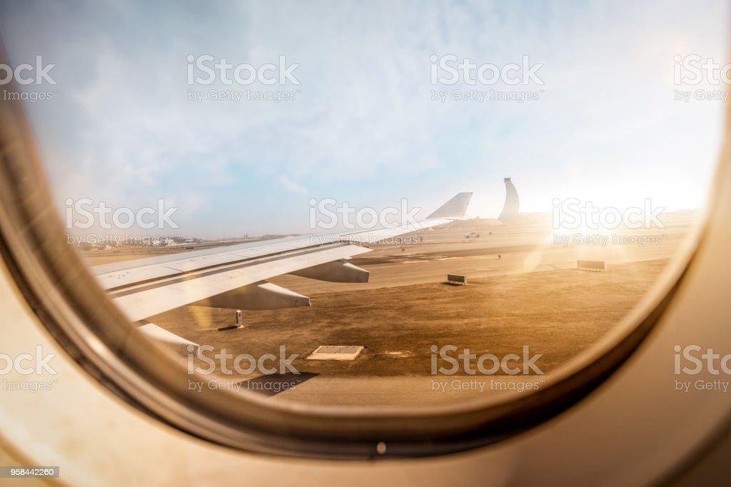 Luftbild aus Flugzeugfenster beim Abheben von der Startbahn des Flughafens während der goldenen Sonnenuntergang – Foto