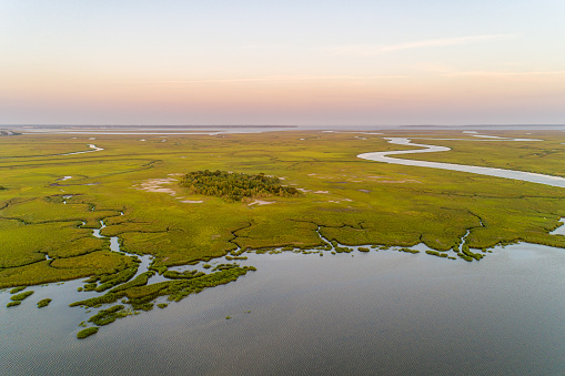 Drone view over the Mackay River just east of Brunswick, Georgia, with Saint Simons and Jekyll Islands in the distance, reflecting late-day sunlight that gives the area its \