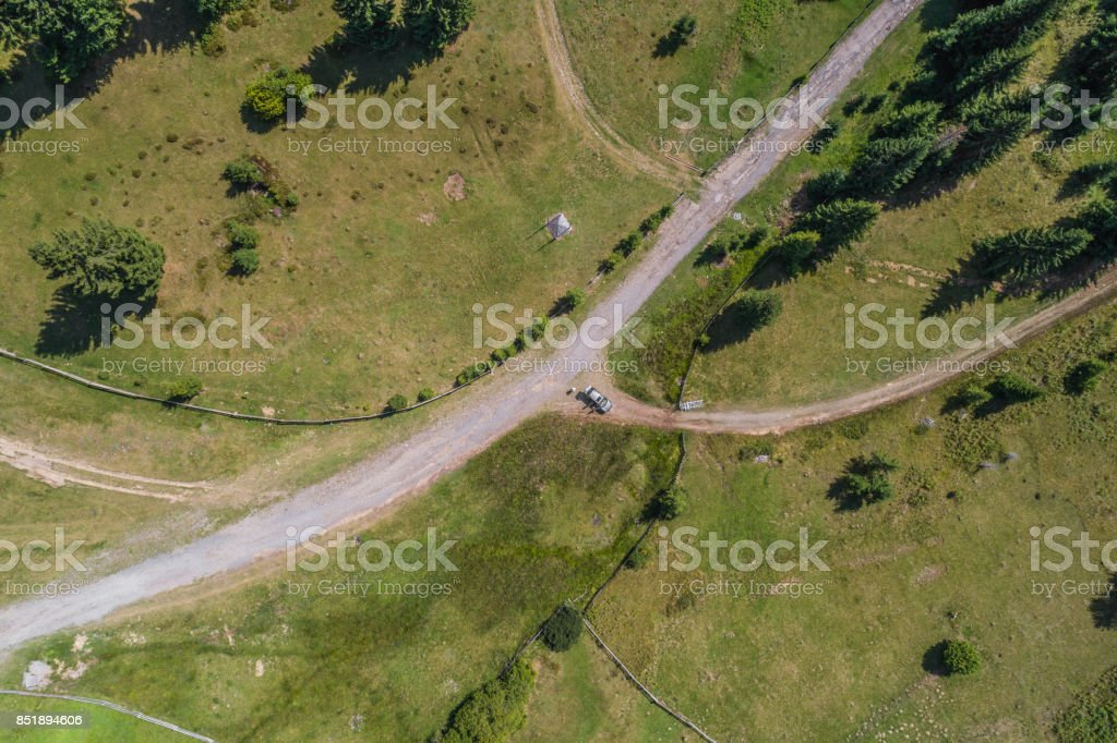 Aerial view over mountain road going through forest landscape stock photo