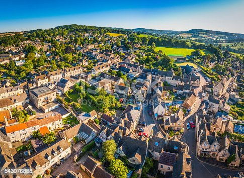Aerial view over the iconic Cotswold village of Painswick, with its honey coloured limestone cottages deep in the bucolic countryside of Gloucestershire, UK, framed by vibrant green patchwork fields and clear blue summer skies. ProPhoto RGB profile for maximum color fidelity and gamut.