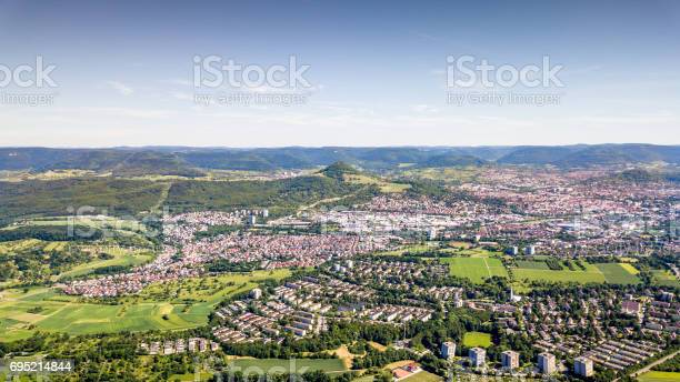 Aerial view over the north of the city of Reutlingen with Mount Achalm and the Swabian Alb Mountain Range in the Background. Panoramic Aerial Drone Shot. South West Germany, Baden Württemberg, Germany.