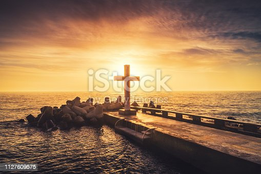 Aerial view over silhouette christian cross in the sea, sunrise shot
