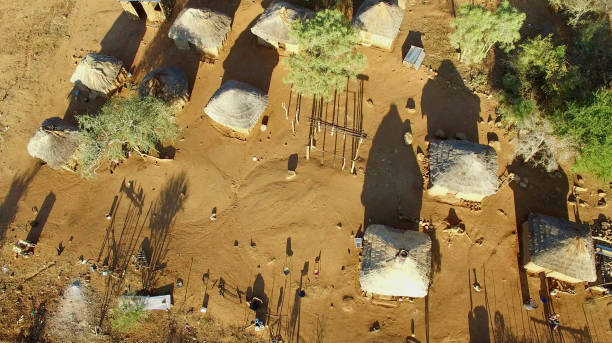 aerial view over small african village - village stock photos and pictures