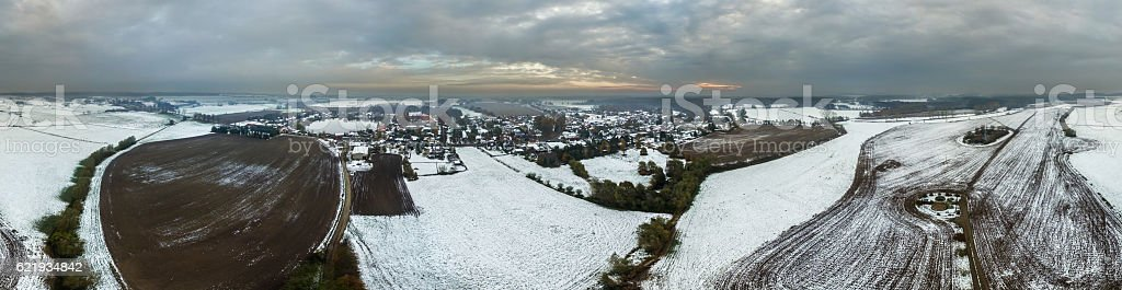 aerial view panorama of a snowy village  with agricultural fields stock photo
