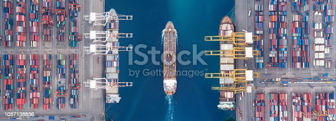 637816284istockphoto Aerial view panoramic oil tanker moving pass sea port warehouse and container ship or crane ship working for delivery containers shipment. Suitable use for energy power or transport or import export to global logistics concept. 1057138856